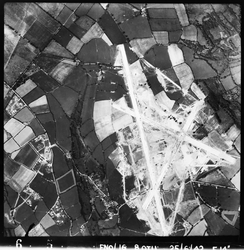 Aerial photograph of Dunkeswell airfield, looking south west, under construction, the perimeter not yet built, the main runway runs vertically, 26 June 1942. Photograph taken by No. 8 Operational Training Unit, sortie number RAF/FNO/16. English Heritage (RAF Photography).