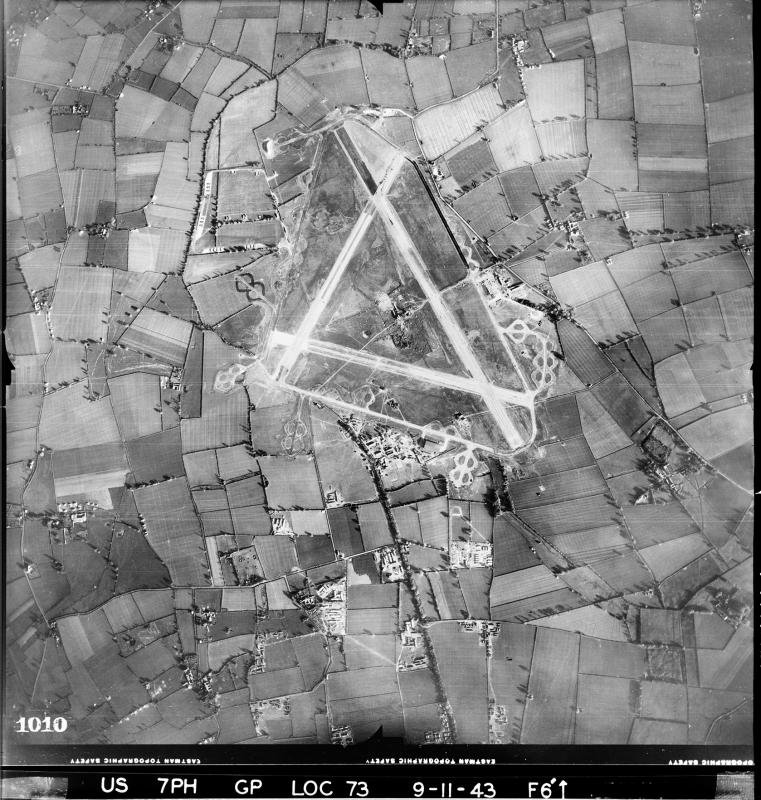 Aerial photograph of Old Buckenham airfield looking east, the bomb dump is upper left, the technical site and sick quarters are below the airfield, 9 November 1943. Photograph taken by 7th Photographic Reconnaissance Group, sortie number US/7PH/GP/LOC73. English Heritage (USAAF Photography).
