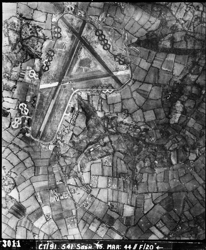 Aerial photograph of Upottery airfield looking west, the main runway runs vertically, barrack sites are to the bottom right of the airfield, 15 March 1944. Photograph taken by No. 541 Squadron, sortie number RAF/CT/91/541. English Heritage (RAF Photography).