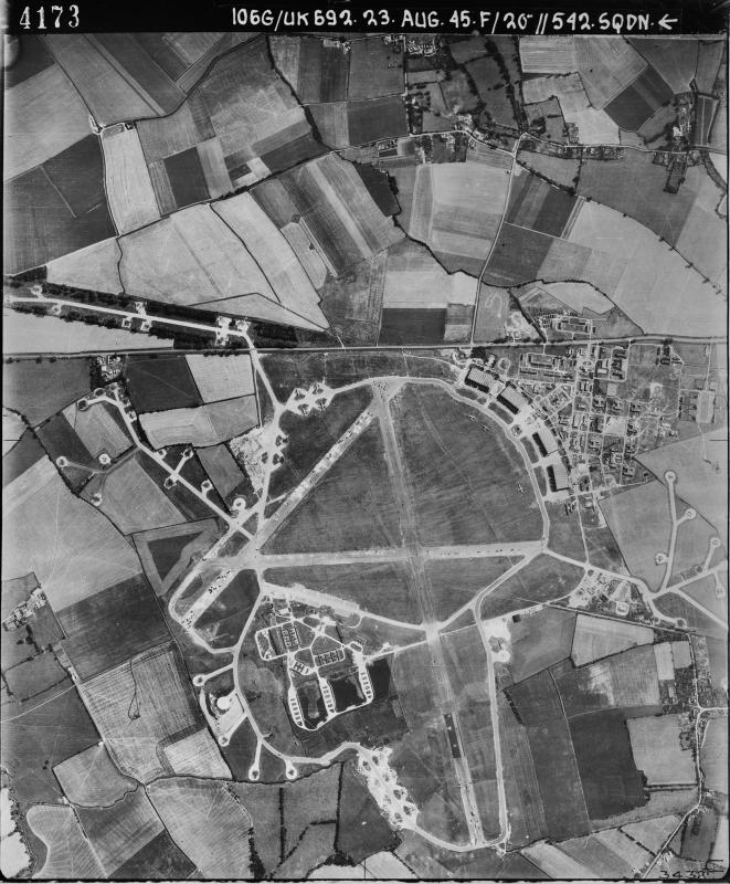 Aerial photograph of Bassingbourn airfield looking east, Whaddon is at the top, the bomb dump is to the left of the main runway, which runs vertically; the control tower and technical site with four C-Type hangars is on the right, 23 August 1945. Photograph taken by No. 542 Squadron, sortie number RAF/106G/UK/692. English Heritage (RAF Photography).