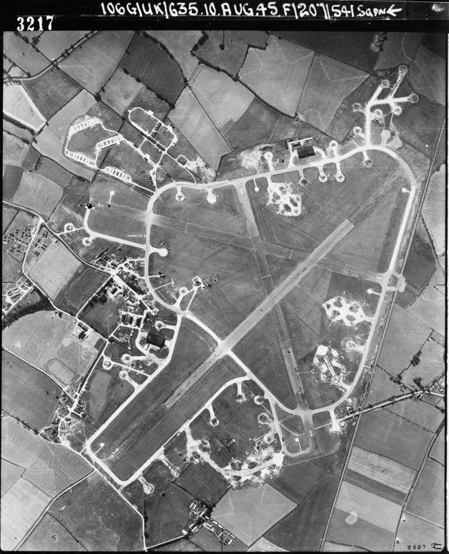 Aerial photograph of Kimbolton airfield looking west, the bomb dump and technical site with a T2 hangar is on the left, 10 August 1945. Photograph taken by No. 541 Squadron, sortie number RAF/106G/UK/635. English Heritage (RAF Photography).