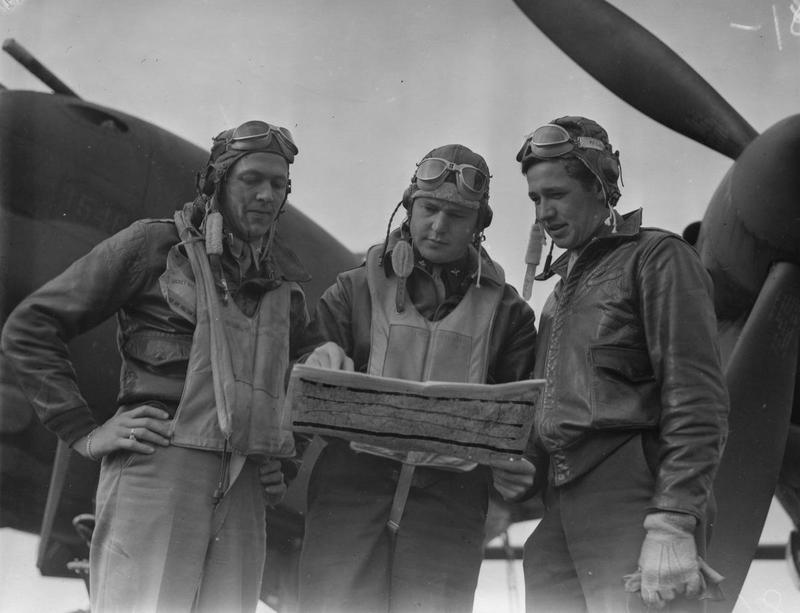 Pilots of the 79th Fighter Squadron, 20th Fighter Group, stand around a map at Kings Cliffe air base before mission over northern France, October 1943. L to R: First Lieutenant Merle B. Nichols, Seattle, Wash.; Major Nathaniel H. Blanton, Earlsboro, Oklahoma and First Lieutenant Richard P. Gatterdam, Columbus, Ohio. Censor has drawn lines across the map. Each of these pilots went on to command one of the squadrons of the 20th Fighter Group. Gatterdam commanded the 55th Fighter Squadron, Nichols the 77th and Blanton the 79th. Printed caption attached to print: 'Lightnings Attack Northern France. Versatile P-38 Lightnings, flashing their power across the English Channel for the first time in a combat role, bring new serial phase into the European Theatre of Operations. Well-trained pilots - some of them already experienced in the other theatres of war - and ground crews swear by their ships. From briefing room to flying line, from runways to skyways and contest with the enemy, each mission represents expert planning by Operations and Intelligence and the brains and sweat of every man who prepares an order or tightens a screw on a prop. Photo shows:- 1st Lt. Merle B. Nichols, Seattle, Wash.; Major Nathaniel H. Blanton, Earlsboro, Oklahoma and 1st Lt. Richard P. Gatterdam, Columbus, Ohio. U.S. Pool/SG/H. Keystone 81.'