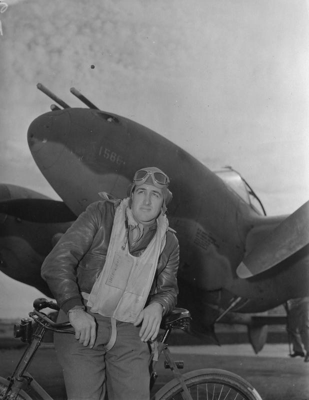 Captain Delynn Anderson of the 20th Fighter Group, with bicycle, in front of P-38H Lightning serial 42-67055 at Kings Cliffe air base, October 1943. Printed caption attached to print: 'Lightnings Attack Northern France. Versatile P-38 Lightnings, flashing their power across the English Channel for the first time in a combat role, bring new serial phase into the European Theatre of Operations. Well-trained pilots - some of them already experienced in the other theatres of war - and ground crews swear by their ships. From briefing room to flying line, from runways to skyways and contest with the enemy, each mission represents expert planning by Operations and Intelligence and the brains and sweat of every man who prepares an order or tightens a screw on a prop. Photo shows:- Capt. Delynn Anderson of Starns, Kentucky. U.S. Pool/SG/H. Keystone 76a.'