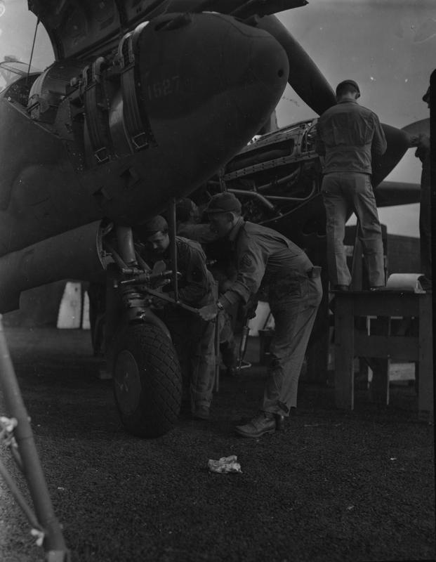 Technical Sergeant Floyd C. Cammon and Sergeant James H. Adams of the 20th Fighter Group at work on a P-38 Lightning at Kings Cliffe air base, October 1943. Printed caption attached to print: 'Lightnings Attack Northern France. Versatile P-38 Lightnings, flashing their power across the English Channel for the first time in a combat role, bring new serial phase into the European Theatre of Operations. Well-trained pilots - some of them already experienced in the other theatres of war - and ground crews swear by their ships. From briefing room to flying line, from runways to skyways and contest with the enemy, each mission represents expert planning by Operations and Intelligence and the brains and sweat of every man who prepares an order or tightens a screw on a prop. Photo shows:- T/Sgt. Floyd C. Cammon, Covington, Okla and Sgt. James H. Adams, Dallas, Texas, checking bombs. U.S. Pool/SG/H. Keystone 50a.'