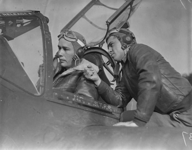Second Lieutenant Mack D. Fall, seated in cockpit, and Second Lieutenant William Gall, both pilots with the 20th Fighter Group at Kings Cliffe air base, October 1943. Printed caption attached to print: 'Lightnings Attack Northern France. Versatile P-38 Lightnings, flashing their power across the English Channel for the first time in a combat role, bring new serial phase into the European Theatre of Operations. Well-trained pilots - some of them already experienced in the other theatres of war - and ground crews swear by their ships. From briefing room to flying line, from runways to skyways and contest with the enemy, each mission represents expert planning by Operations and Intelligence and the brains and sweat of every man who prepares an order or tightens a screw on a prop. Photo shows:- 2/Lt. Mack D. Fall, San Matea, California; and 2/Lt. William Gall, Cincinnati, Ohio. U.S. Pool/SG/H. Keystone 21.'