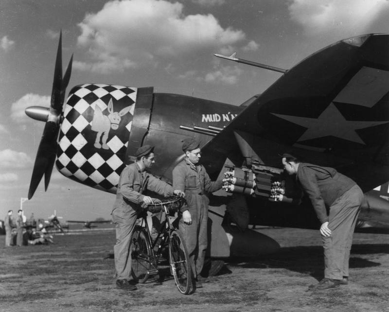 Three ground crew of the 353rd Fighter Group examine the armaments of P-47 Thunderbolt, serial number 42-76141, nicknamed
