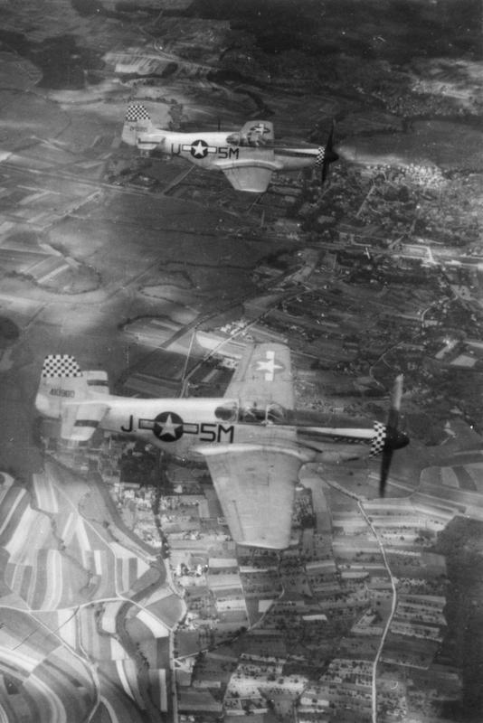 Two F-6C Mustangs of the 15th Tactical Reconnaissance Squadron, 10th Photo Reconnaissance Group, 9th Air Force fly together over countryside. In the foreground is 44-10900 5M-J