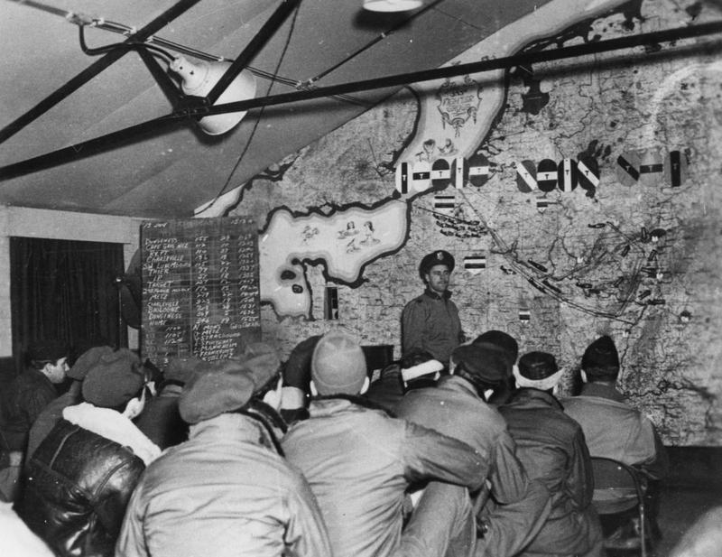 Personnel of the 355th Fighter Group at a briefing before a bomber escort mission, the tail markings of the B-24 Liberators they will escort are exhibited on the map. Handwritten caption on reverse: 'D Lewin in Breifing Room 13/1/45'