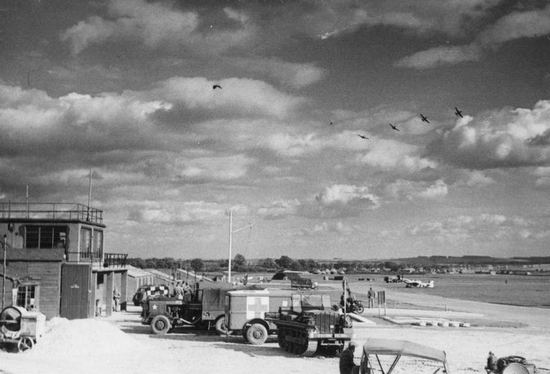 P-51 Mustangs of the 355th Fighter Group break formation, ready for landing, over the ground support vehicles and control tower of Steeple Morden Airfield. Image signed on reverse with the approval of station censor. Handwritten caption on reverse: '355 FG Steeple Morden, Control Tower, read crew + P41 [sic] group peeling off for landing.'