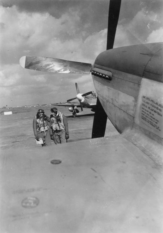 Two pilots of the 355th Fighter Group talk next to a P-51 Mustang. Image stamped on reverse: 'passed for publication 11 April 1945' and Photo Number 405478 Printed caption on reverse is damaged- remains reads: 'USSTAF Foto by SGT. ... Talking over [illegible text]... (see No. 5)'