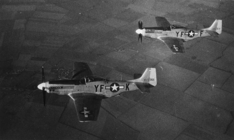 Two P-51 Mustangs of the 358th Fighter Squadron, 355th Fighter group fly in formation over fields.