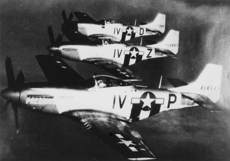 Three P-51 Mustangs of the 369th Fighter Squadron, 359th Fighter Group fly together in formation. The aircraft foreground to background are: (IV-P, serial number 44-14543) nicknamed