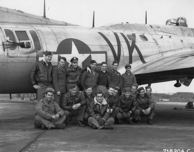 Personnel of the 364th Fighter Group stand in front of a B-17 Flying Fortress of the 303rd Bomb Group at Honington in 1945. Printed caption on reverse: '71620 AC- Colgate Relay Crew of the 364th Fighter Group, 67th Fighter Wing at 8th AFS F-375, Honnington [sic], England. 5/7/45. U.S. AIR FORCE PHOTO.'
