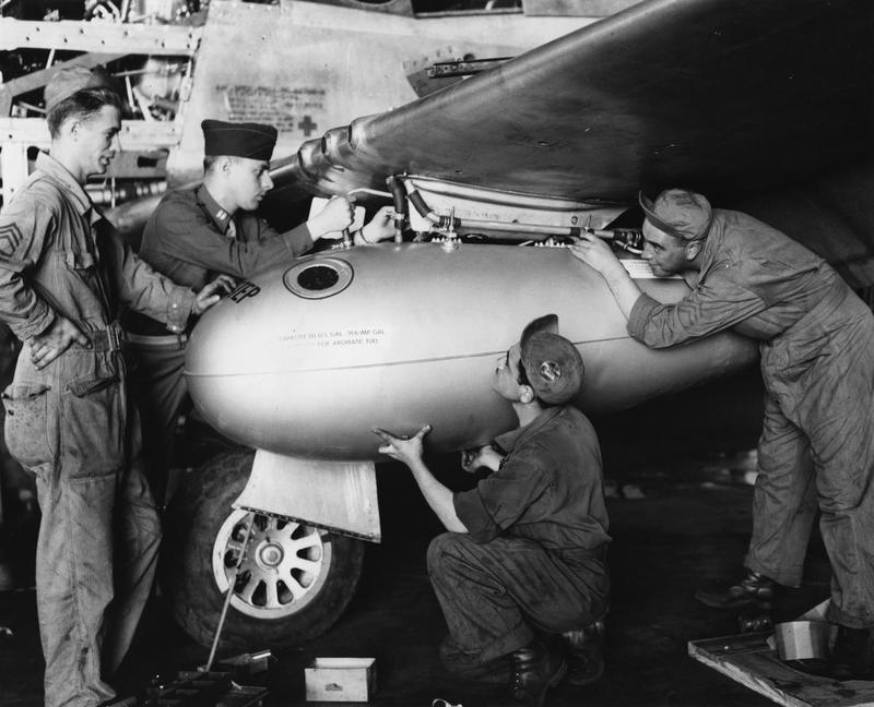 Personnel of the 364th Fighter Group work on a fuel tank from the wing of a P-51 Mustang at Honington, 1944. Printed caption on reverse: '72086 A.C.- Men of the 467th Service Squadron, salvage a fuel tank from the wing of a North American P-51 of the 364th Fighter Group, 67th Fighter Wind at 8th Air Force Station F-375, Honnington [sic], England. 4 August 1944. U.S. AIR FORCE PHOTO.'