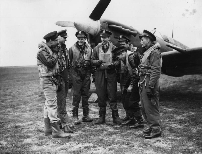 Lieutenant Robert Boock, Lieutenant James Clarke, Captain William T O'Regan, Lieutenant-Colonel Chesley G Peterson, Captain Richard McMinn, Captain Stanley Anderson and Captain Oscar Coen of the 4th Fighter Group with a Spitfire at Debden Passed by the U.S. Army censor on 30 March 1943.  Printed caption attached to print:  'Lt. Col. Chesley G. Peterson D.S.O., D.F.C., U.S. Army Air Force 4th (crossed through with censor's red pencil) Group Britain, who formerly commanded the old Eagle Squadron, seen at an Air Force station somewhere in England with his flight group.'  And '23478. Lt. Col. Chesley G. Peterson (centre) in front of his Spitfire has a talk with his flight group, and they seem very pleased with the raid they are going to carry out. S&G D.M.'  L-R: Bob Boock, Jim Clark, Abe O'Regan, Chesley Peterson, Dick McMinn (in back), Stan Anderson, Oscar Coen.