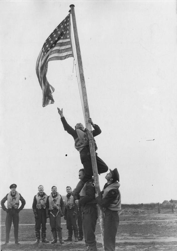 Pilot Officer Kenneth Le Roy Holder stands on the shoulders of Pilot Officer Donald William McLeod to reach out for an American flag flying from a flag pole. A group of American airmen look on. They wear the insignia of the RAF Eagle Squadrons, the forerunners of the squadrons of the 4th Fighter Group. Passed for publication on 27 November 1941. Printed caption on reverse: 'Pilot Officer Kenneth Le Roy Holder from Buena Park, California, stands on the shoulders of Pilot Officer Donald William McLeod from Blackstone, Massachusetts, to fix the American flag at the squadron's flying headquarters in Britain.'