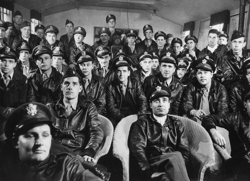 Thunderbolt pilots of the 4th Fighter Group in the briefing room at Debden. The 4th Fighter Group flew P-47 Thunderbolts on missions between March 1943 and February 1944. In the centre of the image, looking straight at the camera is James A. Goodson. On the far right of the shot, wearing a garrison cap, is Lieutenant Paul S. Riley. The two men at the front of the shot, sitting on wicker chairs, are, left to right Lieutenant James A Clark and Lieutenant Spiros S Pisanos. The airman in the back row, with his hand on his chin is Second Lieutenant Kenneth D Peterson. Printed caption attached to print: 'P-47 Thunderbolt pilots listen intently as Intelligence Officers brief them before the start of a mission over France.'