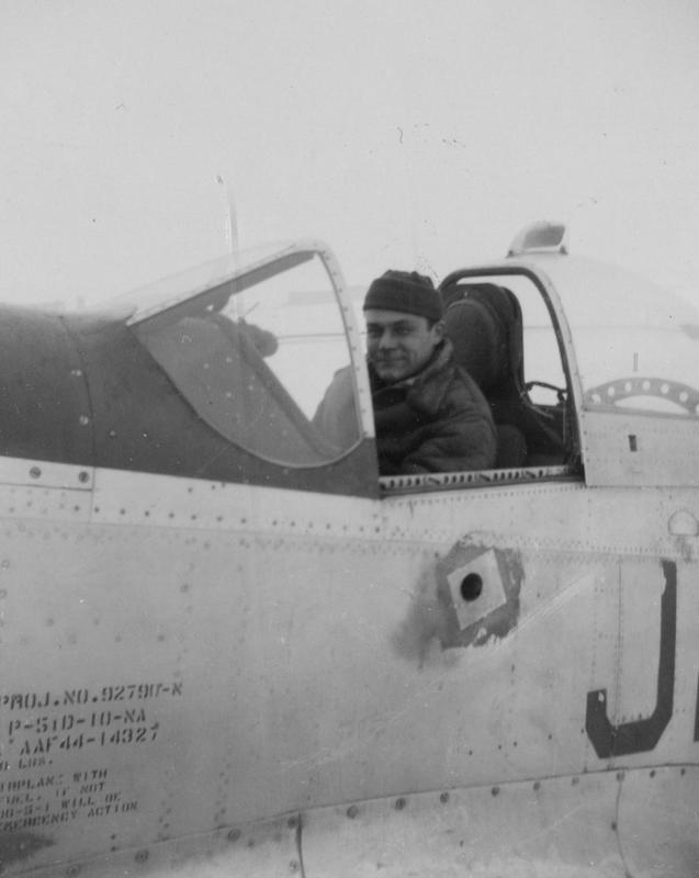 Technical Sergeant H. Leachman of the 479th Fighter Group, sits in the cockpit of a P-51 Mustang (J2-R, serial number 44-14327) flown by Colonel Kyle L Riddle. Handwritten caption on reverse: ' #2 H. Leachman- waiting for the flight. Col Riddle Pilot.'