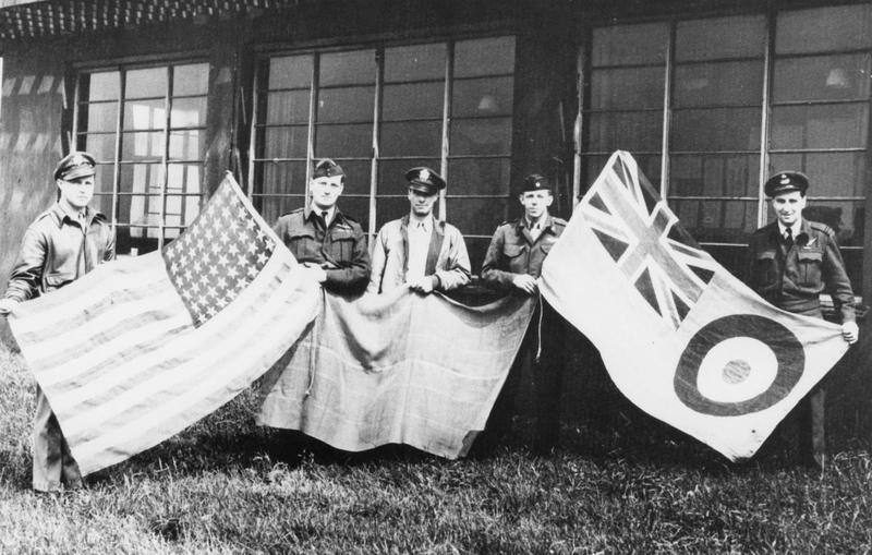 British and American personnel hold up flags at the 496th Fighter Training Group base in Goxhill. Printed caption on reverse: 'P.H.T GREEN COLLECTION PLACE: Goxhill, DATE: 44.'