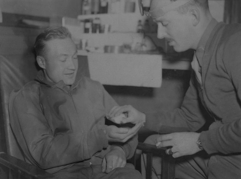 Lieutenant Orville E. Goodman of the 55th Fighter Group receives pills from Flight Surgeon Captain A.R. Garnett at Nuthampstead air base. Passed for publication 12 November 1943. Printed caption attached to print: 'Lt. O.E. Goodman, of Alhambra, Calif., a Lightning P-38 pilot is given vita pills by Flight Surgeon Capt. A.R. Garnett, of Norfolk, Va.'