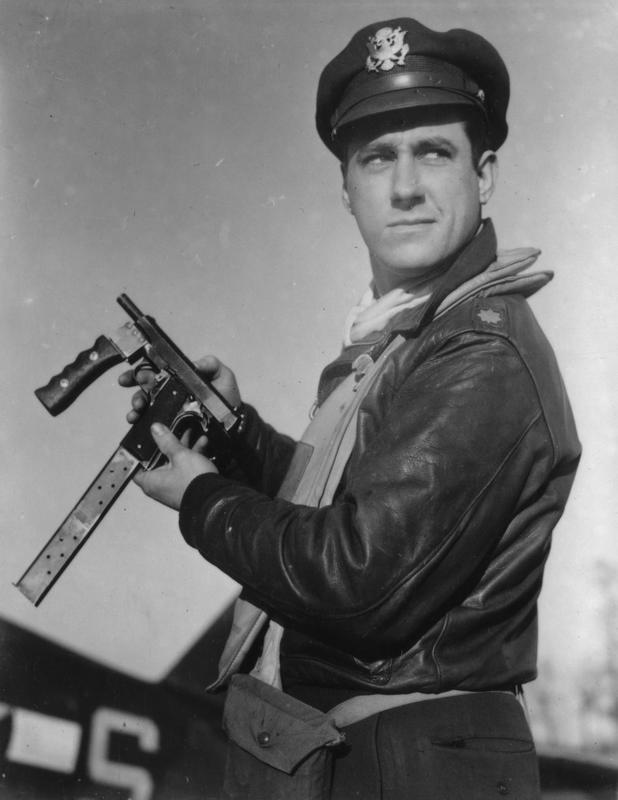 Major David C. Schilling, an ace P-47 Thunderbolt pilot of the 56th Fighter Group, holds a heavily modified 1911 pistol.  The addition of a forward hand-grip and the fact that three magazines have been welding together, likely providing a 21 round capacity, suggest the pistol was possibly modified for full automatic fire.  Schilling was Commanding Officer of the 56th FG between 12 August 1944 and 27 January 1945.  Roger Freeman's writing on reverse of print: 'Dave Schilling with repeater revolver'. Another print copy has a handwritten caption on the reverse written by ace Hub Zemke: 'Summer 1942. Then Major David C. Schilling CO 62nd Fighter Squadron, Bradley Field Conn., showing off his modification to an Army Colt 45. David was up to some engineering gadget all the time. In this case an extended clip was built for more ammunition capacity. A handle had to be built to hold the weapon as it sprayed ammunition all over the landscape. Many a barrel was burned out.'