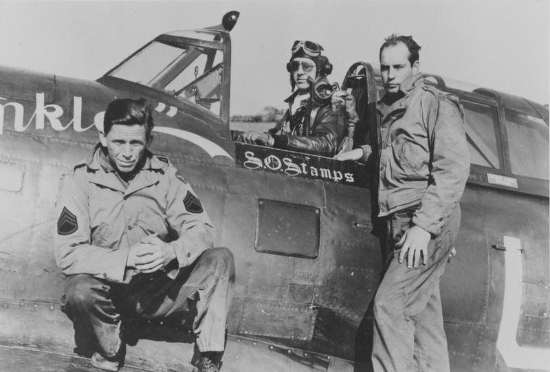 Lieutenant Samuel O. Stamps of the 63rd Fighter Squadron, 56th Fighter Group, with two ground crew, on P-47 Thunderbolt named