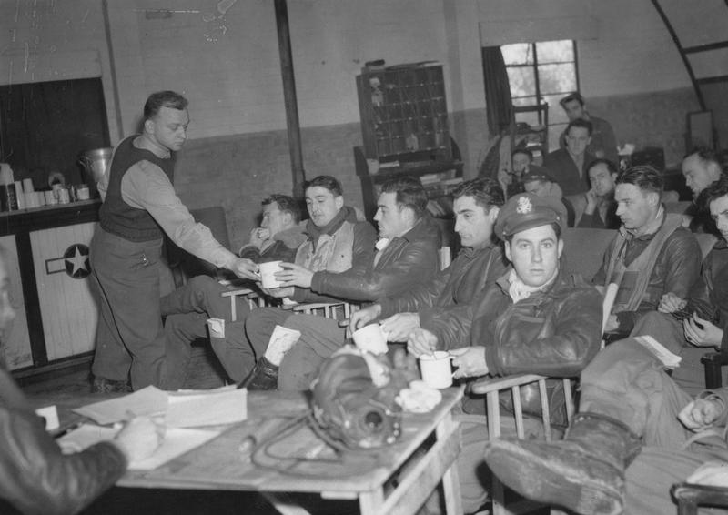 Flight Surgeon Captain George R. Hornig serves up tea to pilots of the 56th Fighter Group in the mess at Halesworth air base. On the front row are, left to right: Captain Francis S. Gabreski, Lieutenant Eugene E. Barnum, an unknown pilot and Lieutenant-Colonel David C. Schilling. Passed for publication 29 November 1943. Printed caption attached to the rest of this series: '