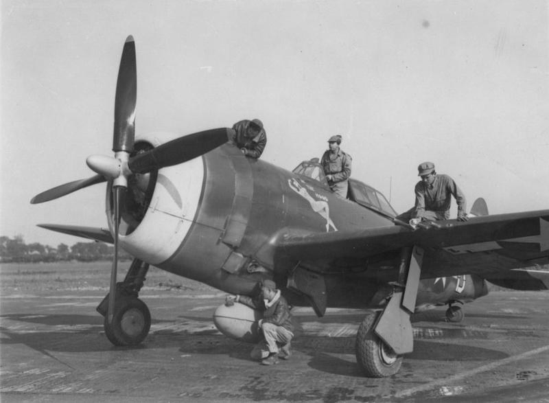 Four ground crew demonstrate the different jobs that an aircraft's ground crew had to perform. One stands in the cockpit with radio equipment, another rubs down the barrels of one of the machine guns, another peers at the edge of the engine cowling and the fourth kneels beside the fuel drop tank. This was probably taken at Halesworth (Holton) air base where the 56th Fighter Group were based between 8 July 1943 and 18 April 1944. The P-47 Thunderbolt is one of the 61st Fighter Squadron's, marked with the code HV-D, serial number 42-7877 and known as
