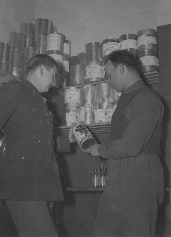 Flight Surgeon Captain George R. Hornig and Lieutenant Otis Trinkle, Messing Officer and part of the 15th Station Complement Squadron, 56th Fighter Group, discuss the nutritional value of food served up in the mess at Halesworth air base. Passed for publication 29 November 1943. Printed caption attached to the rest of this series: '