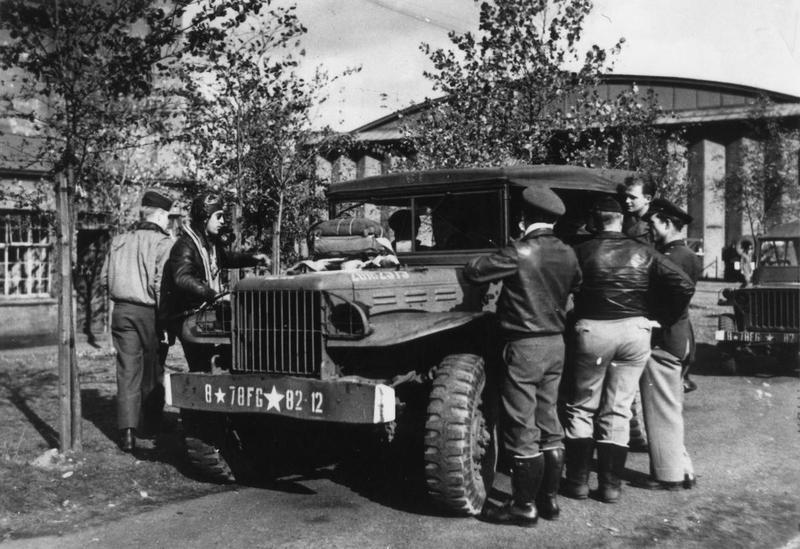 Three pilots (in the boots) of the 82nd Fighter Squadron, 78th Fighter Group, stand around a jeep at Duxford air base with other officers. They are Flight Officer Manuel S. Martinez (left of vehicle), Second Lieutenant William F. Neel and First Lieutenant Jack J. Bernhard (in the white scarf). 1943-1945. 290473 Printed caption attached to the reverse: