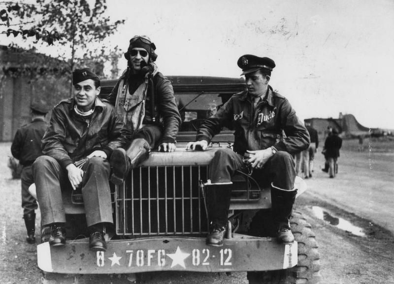 From left to right: Captain Walker L. Boone, Flight Officer Manuel S. Martinez and Flight Officer Gerry E. Brasher, pilots of the 82nd Fighter Squadron, 78th Fighter Group, sit on the bonnet of a Dodge WC (weapons carrier) at Duxford air base. Passed for publication 28 October 1943. Printed caption on reverse: 'Thunderbolts - the