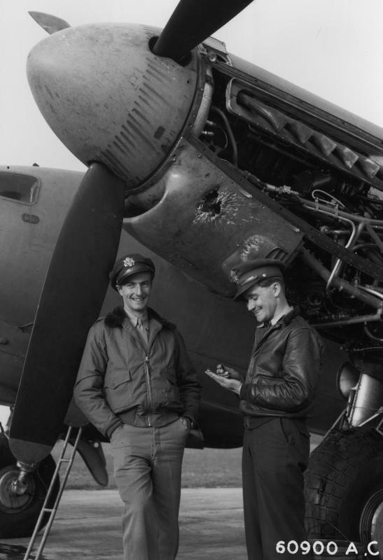 Lt Robert A 'Bob' Tunnell [Pilot] and Lt David A 'Dan' McCarthy [Observer] of the 8 Reconnaissance Squadron (Special)(P), 802 Reconnaissance Group (Special) (P), 8 Reconnaissance Wing (P) with a de Havilland DH98 Mosquito PR XVI NS559 at Watton that has received 'flak' damage to one of its engines, 4 August 1944.    Printed caption on reverse: '60900 A.C.- Lt. Tunnel and Lt. McCarthy of the 654th Bomb. Sqdn. 25th Bomb Group. standing beside a flak damaged DeHavilland