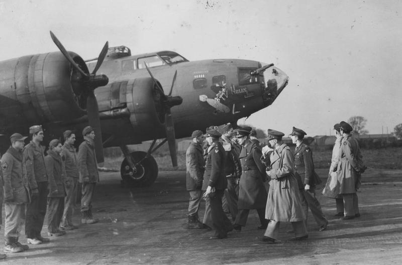 King George VI passes a B-17 Flying Fortress (serial number 41-24352) nicknamed 'Holey Joe' as he meets personnel of the 301st Bomb Group during a royal visit. Image stamped on reverse: 'Copyright Central Press Photos Ltd.' [stamp], 'Passed for Publication 13 Nov 1942.' [stamp], 'P (KING) CCC(USA).'[written annotation] and '232594.' [Censor no.] A printed caption was previously attached to the reverse of the image however this has been removed. Handwritten caption on reverse: '301 , 124352?, Alconbury?.'