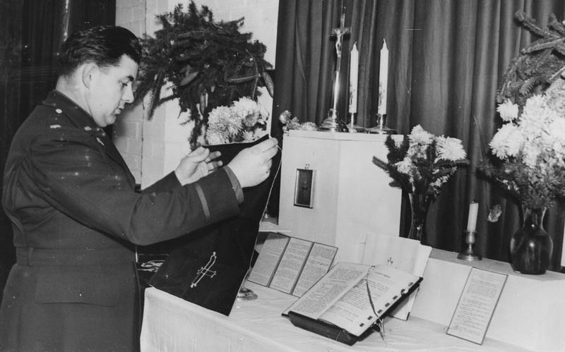 Chaplain Adrian Poletti of the 306th Bomb Group prepares the Altar for Mass inside the station Chapel at Thurleigh.   Image stamped on reverse: 'Copyright Current Affairs Ltd.' [stamp], 'Passed for Publication 28 Jan 1943.' [stamp] and '245678.' [Censor no.]   Printed caption on reverse: 'Preparing for Mass at the American Army Camp in Britain is Chaplain Adrian M Poletti of 203 Oak Street Weehawken , N J. Chaplain Poletti, who is 35 years of age, was formerly at St Michaels School, Union City. His parents reside at 203 Oak St, Weehawken. He sends them all this message-