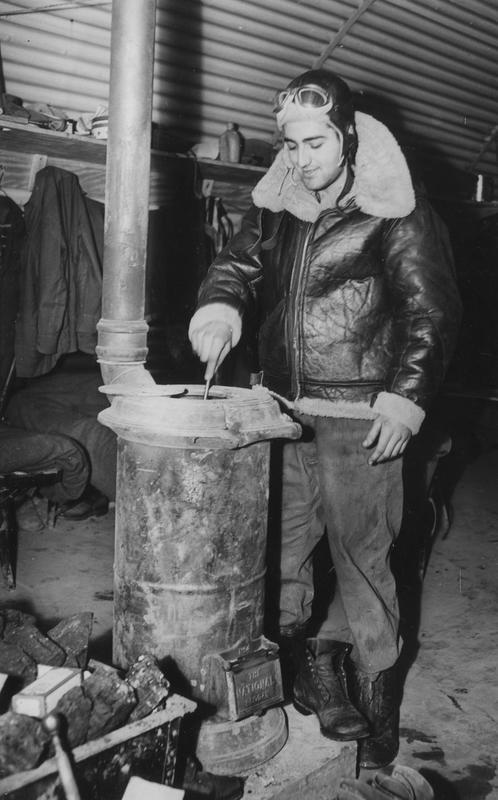 Sergeant Fred Dioquardo of the 303rd Bomb Group stokes the stove inside a hut. Image stamped on reverse: ''Copyright Current Affairs Ltd.' [stamp], 'Passed for publication 28 Jan 1943.' [stamp], '245666.' [Censor no.] Printed caption on reverse: 'Stoking the stove in an American Army Air Force hut somewhere in England. Sergeant Fred Dioquardo, of Bayport, Long Island, asked the photographer to send this message back to his parents and fiance Miss H Sherwood , Maple Ave, Long Island: