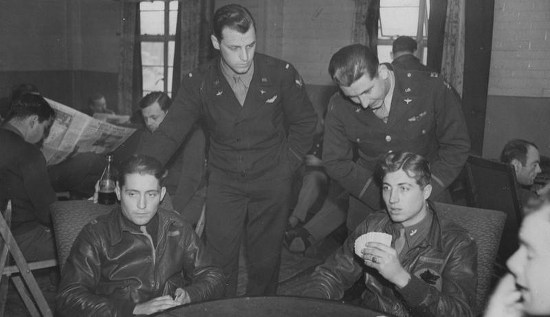 Personnel of the 303rd Bomb Group play cards between raids. A censor has obscured the insignia on the airman's jacket. Image stamped on reverse: 'Copyright Current Affairs Ltd.' [stamp], Passed for publication 9 Apr 1943.' [stamp] and '257513.' [Censor no.] Printed caption on reverse: 'Standing on left watching a card game