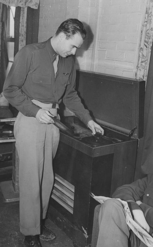 First Lieutenant George J Oxrider a Pilot of the 303rd Bomb Group changes a record. Image stamped on reverse: 'Copyright Current Affairs Ltd.' [stamp], 'Passed for Publication 9 Apr 1943.' [stamp] and '257527.' [Censor no.] Printed caption on reverse: 'Changing a record on the radiogram at his British base, is 1st Lieut. (Pilot) George J. Oxrider of 437, Allwen Street, Dayton, Ohio, holder of the D.F.C., the Air Medal and 2 Oak Leaf Clusters. A pre-medical student at the University of Cincinnati and aged 25 Oxrider sends this message to his parents at Allwen St: