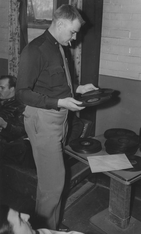Major Clemens K. Wurzbach, of the 303rd Bomb Group, tries out a new gramophone record. Image stamped on reverse: 'Copyright Current Affairs Ltd.' [stamp], 'Passed for Publication 9 Apr 1943.' [stamp] and '257520.' [Censor no.] Printed caption on reverse: 'Trying out some new gramophone records at a British base Major Clements K. Wurzbach used to be at a ranch. His home is at Route No.4. Box 156, San Antonio, Texas, where his parents live. Now a pilot and cammander of his squadron he has been awarded the Air Medal for his part in 7 raids. He is 27 and was educated at St. Mary's University, San Antonio. U.69 Not to be published before 20th April, 1943.'