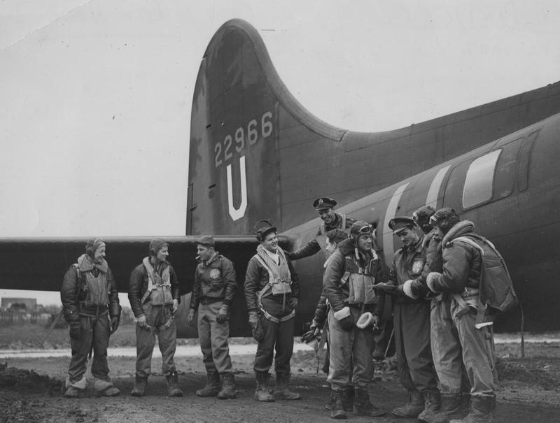 A bomber crew of the 303rd Bomb Group, with their B-17 Flying Fortress (GN-V, serial number 42-2966), after a raid on Germany.   From left to right they are:  Sergeant Ward W. Kirkpatrick (Kalispel, Montana);  Technical Sergeant Lucian W. Means, (Luguna Beach, California);  First Lieutenant Milton K. Conver (Cincinnatti, Ohio);  Second Lieutenant John W Dillenger (Avoca, Iowa), Co-Pilot;  Captain B.B. Southworth (Columbus, Ohio), Pilot;  Sergeant Jack Belk (Temple, Texas);  Sergeant William Fleming (Burdine, Kentucky);  First Lieutenant Jon R. Schueler (Milwaukee, Wisconsin);  Technical Sergeant Edward J. Doughty (Philadelphia, Pennsylvania);  and Technical Sergeant Waldo B. Brandt (Denver, Indiana).   Image stamped on reverse: 'Copyright Barratt's Photo Press.' [stamp], 'Passed for Publication 8 Mar 1943.' [stamp] and USA (BRI) CCC.' [annotiation] Printed caption on reverse: 'BT.4323D The crew of one of the Flying Fortresses of the U.S.Army Air Corps which carried out their first raid on Germany. Sergt. Ward W. Kirkpatrick (Kalispel, Mont.) T/Sgt Lucian W. Means, (Luguna Beach, Cal.) 1 Lt Milton K. Conver (Cincinnatti, Ohio) 2nd Lt. John W Dillenger (Avoca, Iowa) Co-Pilot Capt B.B. Southworth (Columbus, Ohio) Pilot Sgt. Jack Belk (Temple, Tex.) Sgt. William Fleming (Burdine, KY) 1st Lt. Jon R. Schueler (Milwaukee, Wis.) T/Sgt Edward J. Doughty (Philadelphia, Penn.), T/Sgt Waldo B. Brandt (Denver, Ind). Censor No.245872.'