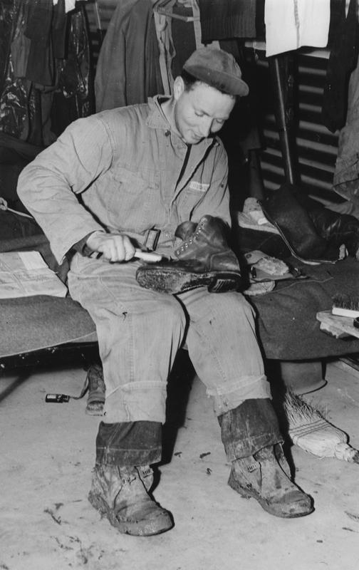 Corporal John R. Hughes, of the 303rd Bomb Group, cleans his boots. Image stamped on reverse: 'Copyright Current Affairs Ltd.' [stamp], 'Passed for Publication 28 Jan 1943. [stamp] and '245686.' [Censor no.] Printed caption on reverse: ''Cleaning the English mud from his boots is Cpl. John R. Hughes, of 101, West 91 St. N.Y.C. Aged 22, he formerly worked in his father's business at 752 Broadway, N.Y.C. His parents, Mr and Mrs. Hughes, live at W. 91 Street. Cpl Hughes was educated at Commerce High School. And here is his message -