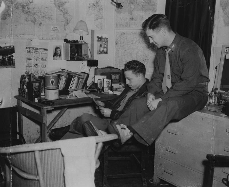 First Lieutenant Ehle H. Reber and Captain Lloyd R. Cole, both of the 303rd Bomb Group, relax in Reber's quarters. Image stamped on reverse: 'Associated Press.' [stamp], 'Passed for Publication 25 Jan 1943.' [stamp] and '245295.' [Censor no.] Printed caption on reverse: 'How the boys live and work at Flying Fortress Station in England. Wide World Photo shows: 1st Lieut. Ehle H. Reber, Malin, Oregon (left) and Captain Lloyd R. Cole, Winchester, KY. In Reber's quarters, which, as you see, he's turned into a homey den. WW/ALA.'