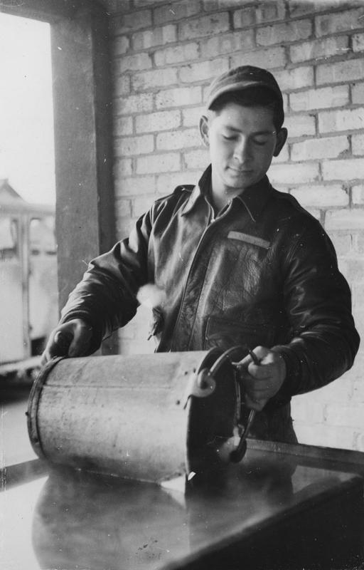 Sergeant Bernard Aleys Gergash, of the 303rd Bomb Group, fills a water bucket. Image stamped on reverse: 'Copyright Current Affairs Ltd.' [stamp], 'Passed for Publication 16 Dec 1942. [stamp] and '238749.' [Censor no.] Printed caption on reverse: '32a. Filling the bucket is Sgt. Bernard Aleys Gergash, of 1025 Union Ave., Chicago Heights. Aged 24, he worked as a radio operator with the C.A.A.'