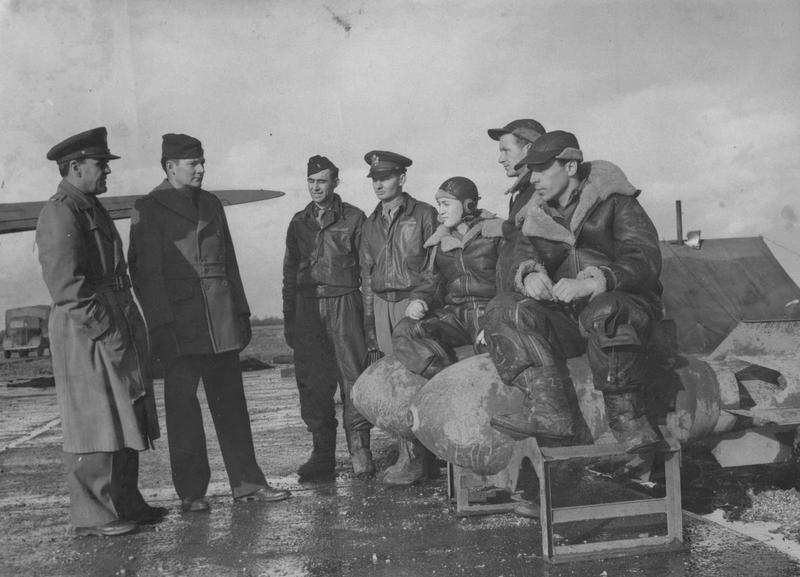 Two Intelligence Officers - Major John B. Wright, Group Intelligence Officer of New York and Major Ralph Oliver, Operations Officer of Palo Alto, California, both on the left - of the 306th Bomb Group interrogate a bomber crew, sat atop bombs, after a mission. The five bomb crew from left to right are Lieutenant Frank Yaussi of Glendale, California; Lieutenant R.J. Salitrink of Alhambra, California; Staff Sergeant Donald Tunstall of Darlington, South Carolina; Staff Sergeant Raymond R. Erikson of Chicago; and Staff Sergeant Charles D. Hill of Baltimore.   Image stamped on reverse: ' Associated Pres.' [stamp], 'Reveiwed and Passed as censored '2 Feb 1943.' [stamp] and '246550.' [Censor no.] Printed caption on reverse: 'AMERICAN AIRMEN WHO MADE FIRST DAYLIGHT RAID ON GERMANY. Associated Press Photo shows:- Intelligence officers questioning members of a Fortress crew, the first to bomb Wilhelmshaven. Left to right: Major John B. Wright, Group Intelligence Officer of New York; Major Ralph Oliver, Operations Officer of Palo Alto Calif., Talking to Lt. Frank Yaussi of Glendale, Calif; Lt. R.J. Salitrink of Alhambra, Calif.; S/Sgt Donald Tunstall of Darlington, S. Carolina,; S/Sgt Raymond R. Erikson of Chicago; and S/Sgt Charles D. Hill of Baltimore. TET 254773. I243.' Censors have amended each occurence of 'Intelligence Officer' to read 'Officer.'