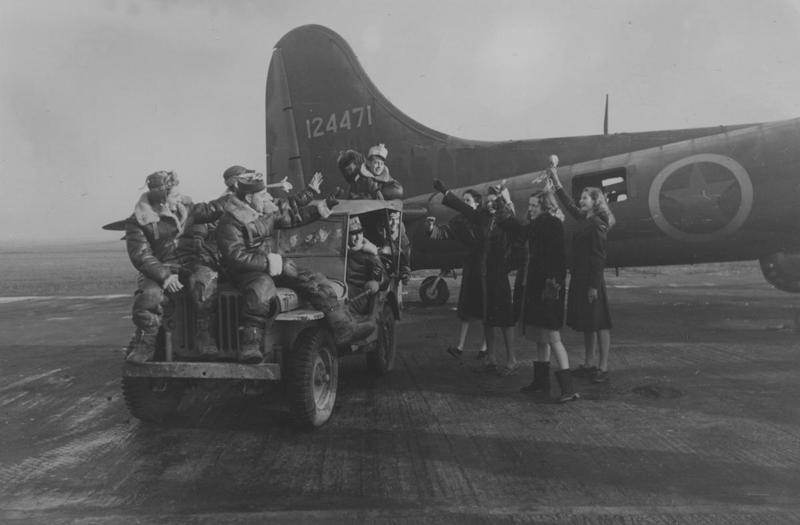 A bomber crew of the 306th Bomb Group wave to Picture Post Girls in front of a B-17 Flying Fortress (serial number 41-24471) nicknamed