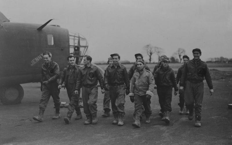 The crew of the B-24D Liberator, serial number 41-23778, named,  Jenny, in the 44th Bomb Group, returns to Shipdham following a raid on Germany, 27 January 1943.  The insignia attached to the breast of several crew members jackets has been censored.   Image stamped on reverse:  'Barratt's Photo Press.' [stamp], 'Passed for publication 29 Jan 1943.' [stamp].   Printed caption on reverse :  'First American raid on Germany.  Flying Fortresses and Liberators of the U.S. Army Air Corps Carried out their first raid on Germany on Wednesday last. O.PS.  The crew of the Liberator, Jenny, leaving after the U.S. raid on Germany. (Barratt's. 29/1/43).'