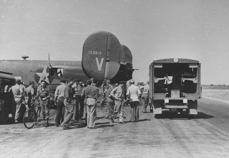 A medical truck and ground personnel of the 44th Bomb Group on standby as a B-24D Liberator with the RCL, V, and the serial number 41-23813, named, Victory Ship, returns from a mission.     ~    Image via Colonel William R Cameron.