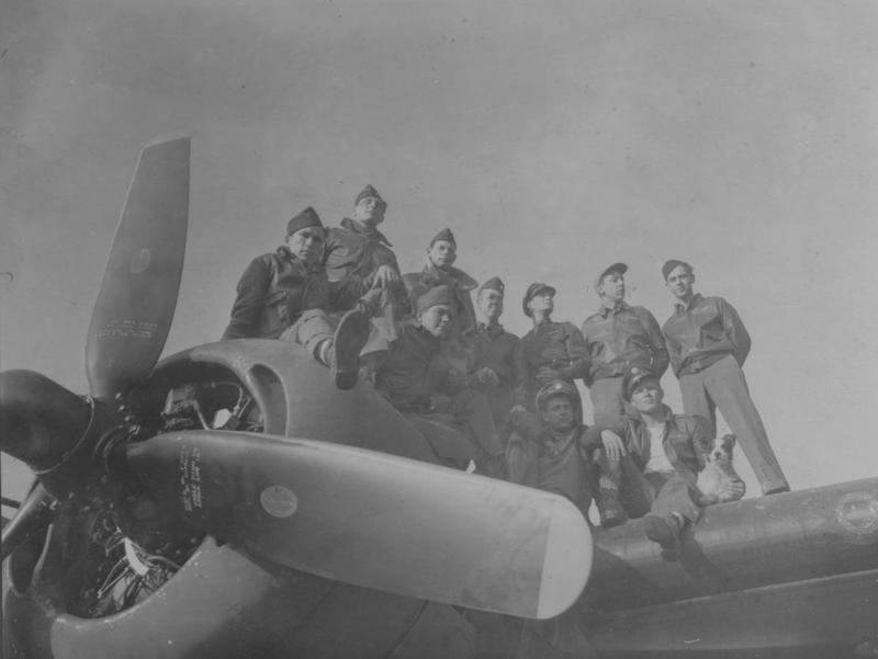 Personnel of the 389th Bomb Group stand atop the engine of a B-24 Liberator (serial number 42-40787) nicknamed