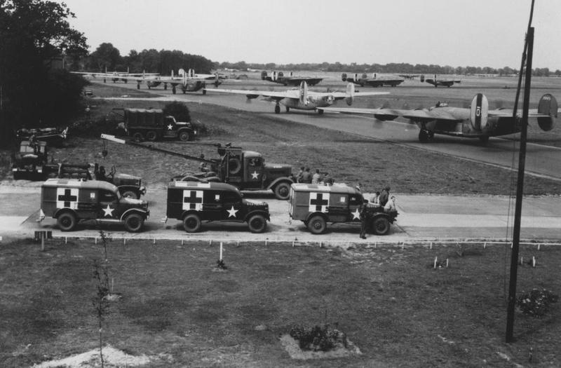 Field Ambulances standby as B-24 Liberators of the 44th Bomb Group line up for takeoff at Shipdham. Image has been signed on reverse with an illegible signature. Handwritten caption on reverse: '281-66-76.'