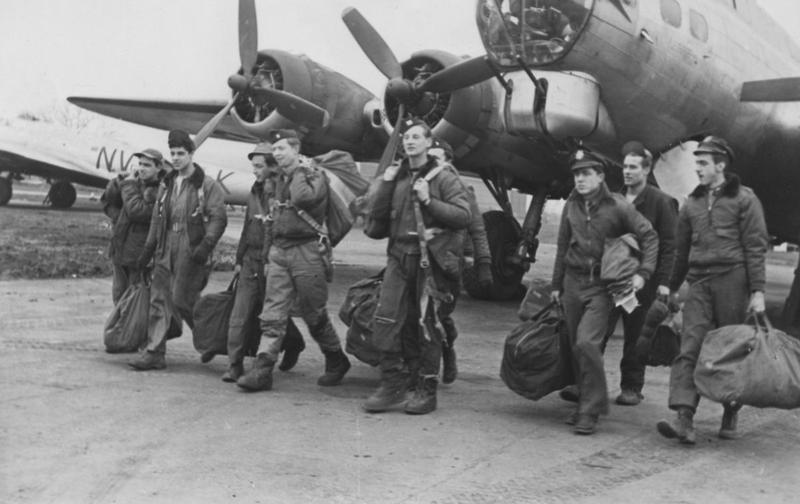 A bomber crew of the 92nd Bomb Group return to Podington following a mission flying B-17 Flying Fortresses to Wittenberg. A B-17 Flying Fortress (NV-K, serial number 42-29994) is visible in the background. Image stamped on reverse: 'Passed for Publication 23 Feb 1945' [stamp]. ' News Chronicle Copyright Picture' [stamp]. Printed caption on reverse: 'Crew back from Wittenberg.'