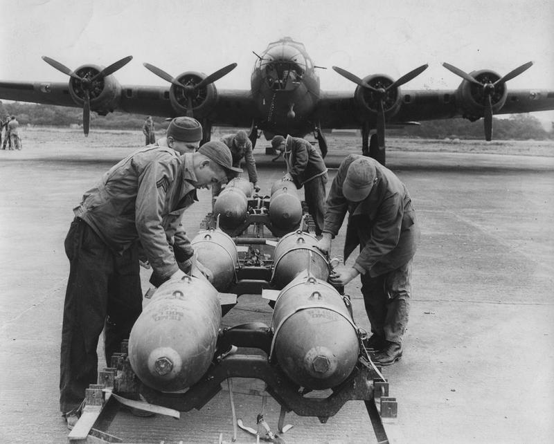 Ground crew of the 92nd Bomb Group load bombs onto a B-17 Flying Fortress at Bovingdon. Image stamped on reverse: 'Planet News Passed by Censor.'[stamp]. 'Return to P.I.D' [stamp].'Copyright B.L.Davis'[stamp]. Printed caption on reverse: 'NOT TO BE PUBLISHED BEFORE THE DAILY NEWSPAPERS ON TUESDAY - 20th October 1942. AMERICAN FORTRESS BOMBERS IN BRITAIN PREPARE FOR NEXT MOVE. These pictures of American Fortress bombers were taken at the operational station of the United States Army Air Forces operating in Britain. The bombers have carried out many successful raids on enemy territory, but have so far operated by daylight only. They are now busy at their base somewhere in England, getting ready for their next surprise attack. PHOTO SHOWS:- Men of the ground staff of the United States Army Air Force, busy at bombing-up the 'planes just before a take-off at the operational 'drome somewhere in England. AND 19th October, 1942. PN-s CENSOR NO:227604/5/6/7/8.'